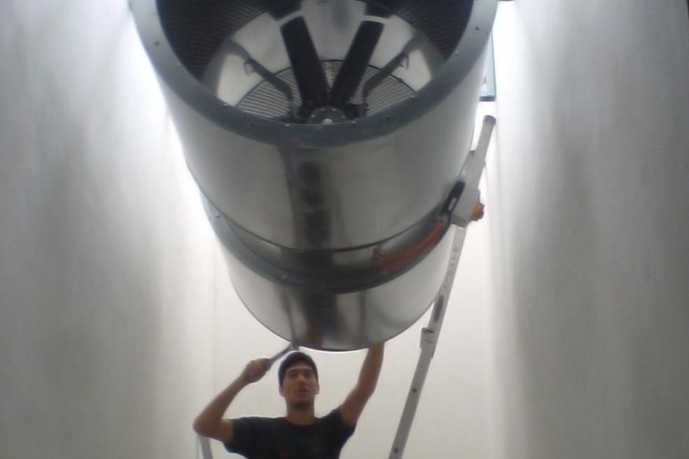 técnico a instalar motor para ventilação de garagem